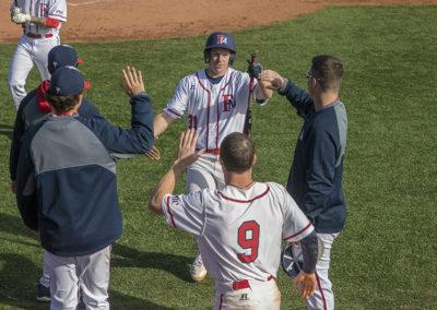 Baseball players cheer following a run scored.