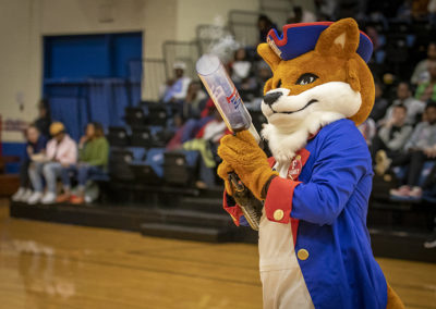 Frank the Fox FMU's mascot shoots of t-shirts during a game break.